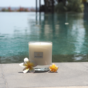 Escape Meditation Candle next to outdoor swimming pool with frangipani flowers