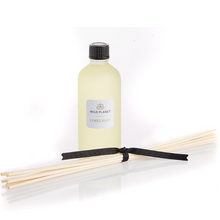 Natural Diffuser Refill in Limelight in glass bottle with reed sticks tied with ribbon