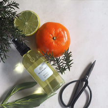 Mood Boost Natural Room Spray using Essential Oils - glass bottle next to fresh lime and mandarin