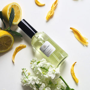 Essential Oil Room Spray glass bottle in lemon verbena fragrance with fresh cut lemons and flowers