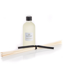 Midsummer Natural Diffuser Refill glass bottle next to reed sticks tied with black ribbon