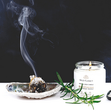 Lit Revitalise Candle Jar with rosemary sprig next to smoking sage bundle on shell dish