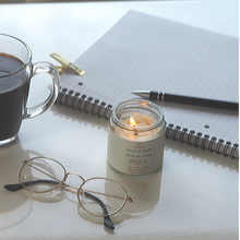 Revive Lime and Ginger lit Candle Jar with citrine next to cup with black coffee and notepad