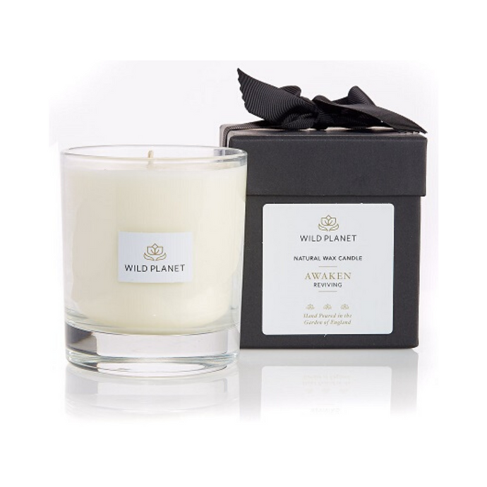 Clear glass Awaken aromatherapy candle next to branded black box with white label tied with ribbon
