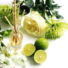 Limelight Natural Reed Diffuser glass bottle and reed sticks next to fresh cut limes and flowers