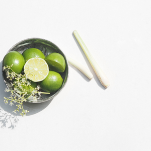 Bowl of fresh limes with one cut in half with flowers on top next to fresh lemongrass