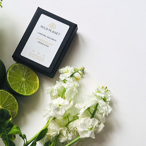 Limelight Luxury Wax Melts box next to a fresh lime cut in half and fresh white flowers