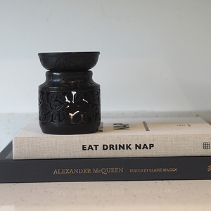 Oil Burner Wax Melter in black soapstone with lit tea light inside on top of two books