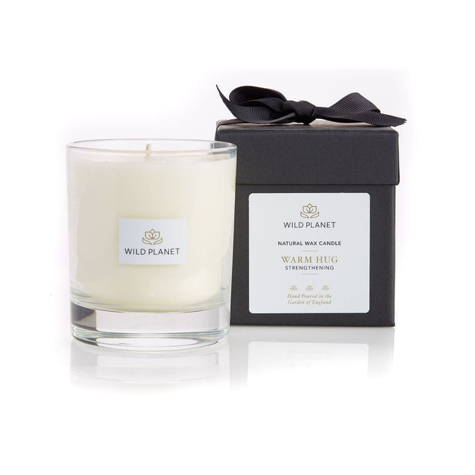 Warm Hug Candle in front of black branded box tied with black ribbon by Wild Planet Products