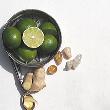 Bowl of fresh limes, one cut in half, next to ginger root on spoon and natural citrine crystals