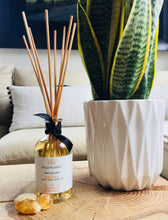 Natural Revive Home Fragrance Reed Diffuser on wooden table next to plant pot and citrine crystals