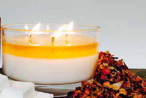 Lit 3 wick aromatherapy candle in glass container next to dried rose petals