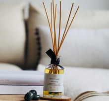 Revitalise Natural Reed Diffuser with Green Moss Agate gemstones on wooden table next to sofa