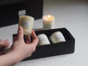 Hand holding one votive from a Trio of Botanical Candles Gift Set next to one lit votive