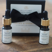Essential Oil Duo Set in Uplift and Energise in front of black ribbon tied box on wooden table