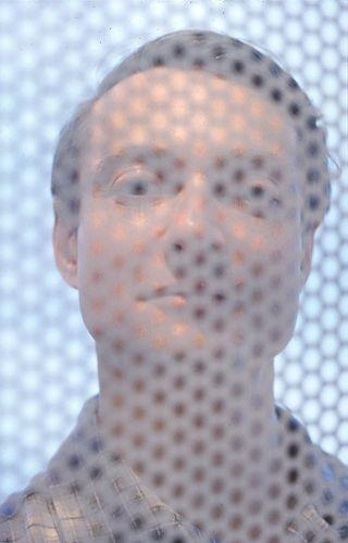 Dan Budnik - Roy Lichtenstein Behind Ben-Day Screen, New York, 1964