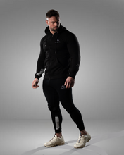 product shot of a male wearing a zipped black hoodie and joggers