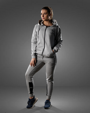 product shot of a female wearing a zipped grey hoodie and joggers