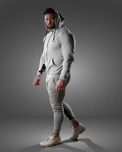male wearing a zipped grey gym hoodie and gym joggers