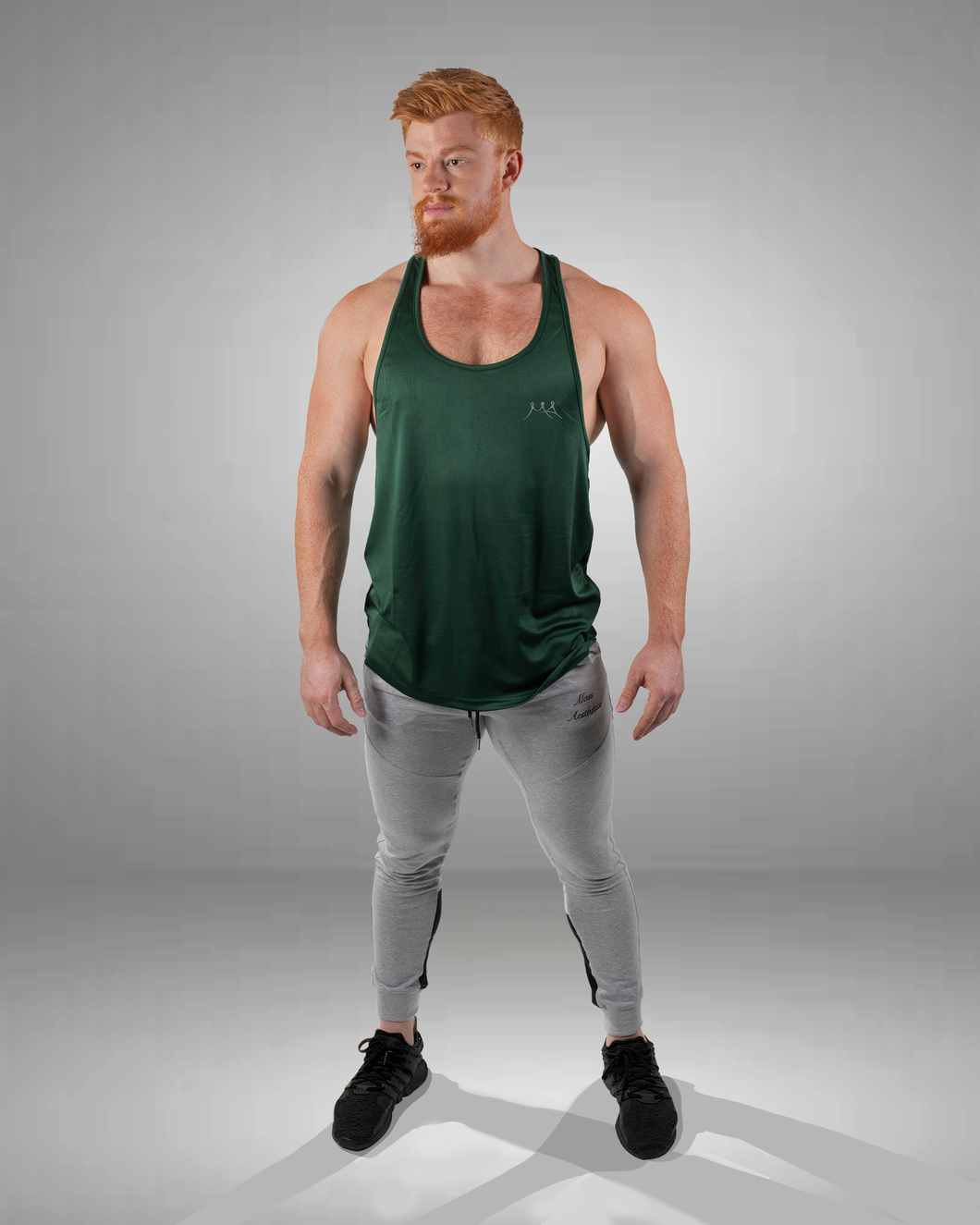male wearing a myrtle green gym stringer vest