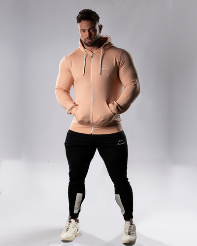 product shot of a male wearing a zipped dusty pink hoodie and joggers