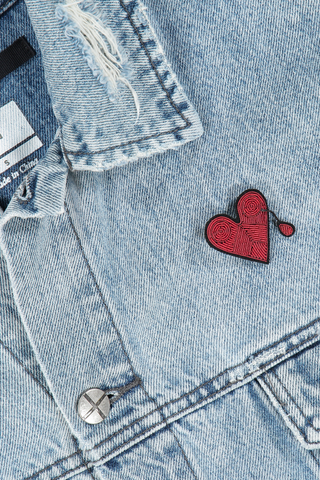 Image of Macon & Lesquoy Injured Heart Pin on jean jacket