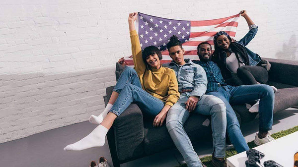 Four young friends are posing in front of a couch while holding the American Flag