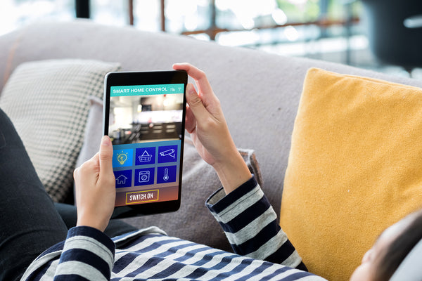 Woman using smart home app on couch