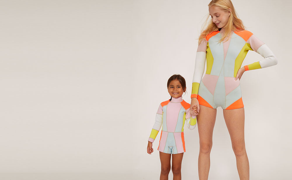 Image featuring Mommy and me matching color block wetsuits.