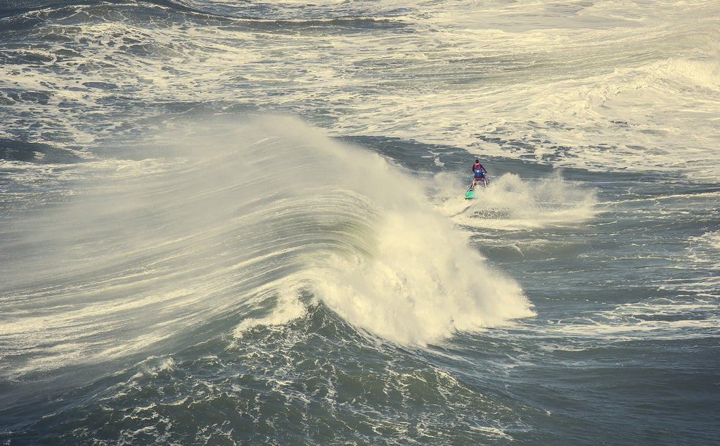 Image of a wave crashing and person riding a jetski in Nazare, Portugal