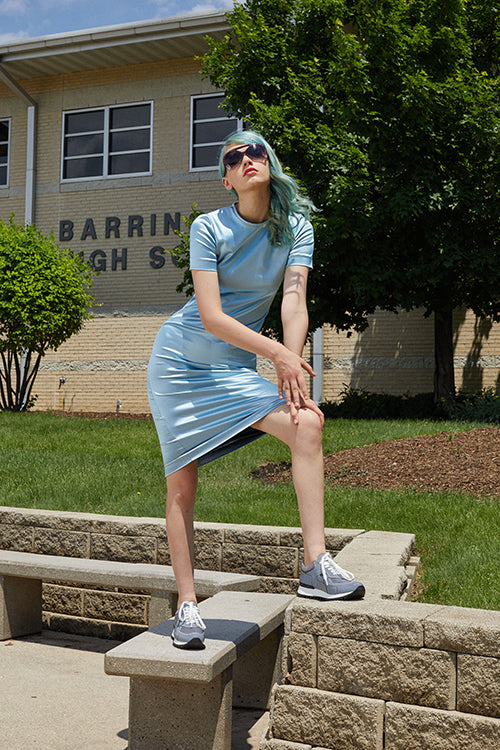 Cynthia Rowley Resort 2019 Collection features a silky, mid-length dress in sky blue styled with grey sneakers, and sunglasses with studded frames.