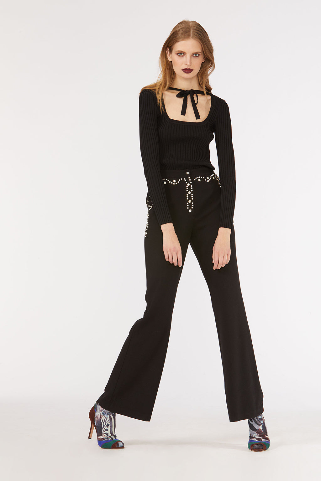 Cynthia Rowley Fall 2018 look 13 featuring black pants with rhinestone detail and a black ribbed scoop neck sweater with neck-tie.