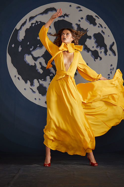 Cynthia Rowley Spring 2019 look 14 featuring a yellow maxi dress with deep V-neck, long bell sleeves, and a large bow around the neck