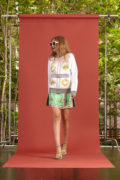 Cynthia Rowley Resort 2017 look 15 featuring a cream sweatshirt and a green printed mini skirt