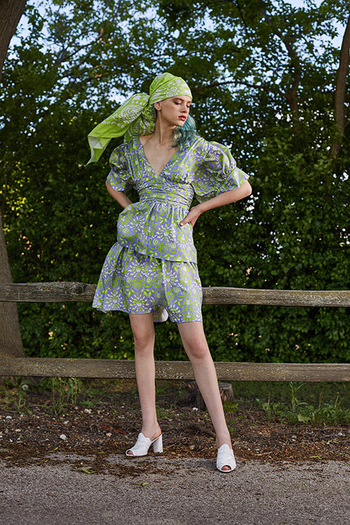 Cynthia Rowley 2019 Resort Collection features a floral printed dress with a plunging neckline, belted high waist, and tiered bottom.