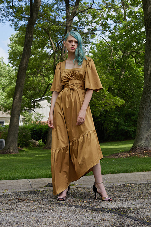 Cynthia Rowley 2019 Resort Collection features a saffron colored asymmetrical maxi dress belted at the high waist, and finished with gold and blush colored heels.