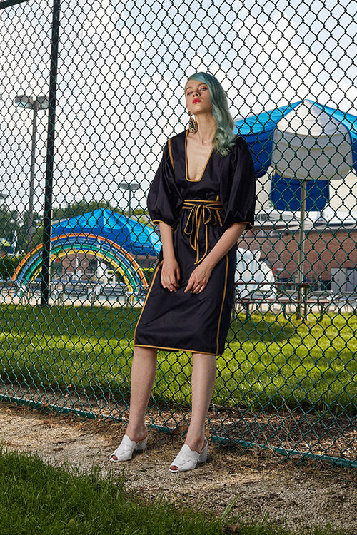 Cynthia Rowley 2019 Resort Collection features a belted mid-length black dress with gold stripes along the sides.