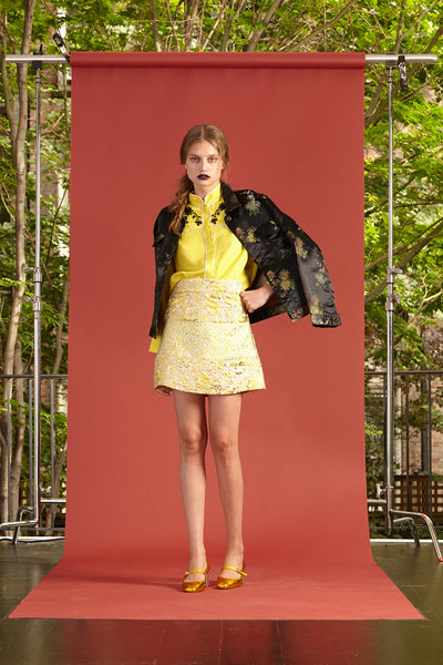 Cynthia Rowley Resort 2017 look 20 featuring a yellow top, light yellow mini skirt, and printed black blazer