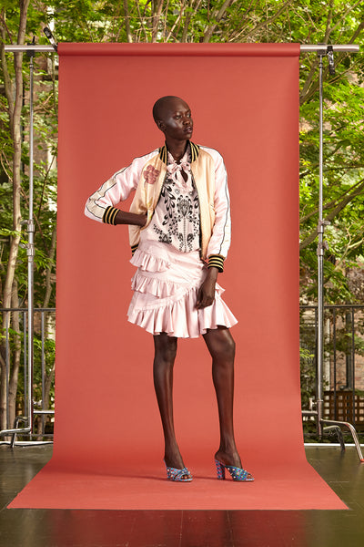 Cynthia Rowley Resort 2017 look 22 featuring a light pink and black blouse, pink ruffle mini skirt, and a light pink bomber jacket