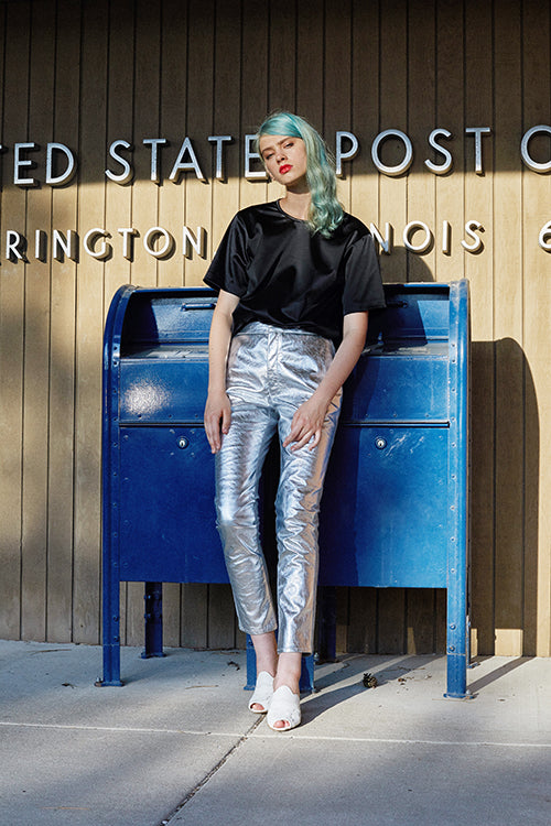 Cynthia Rowley 2019 Resort Collection features high-waisted silver metallic pants paired with a silky, black, scooped neck top.