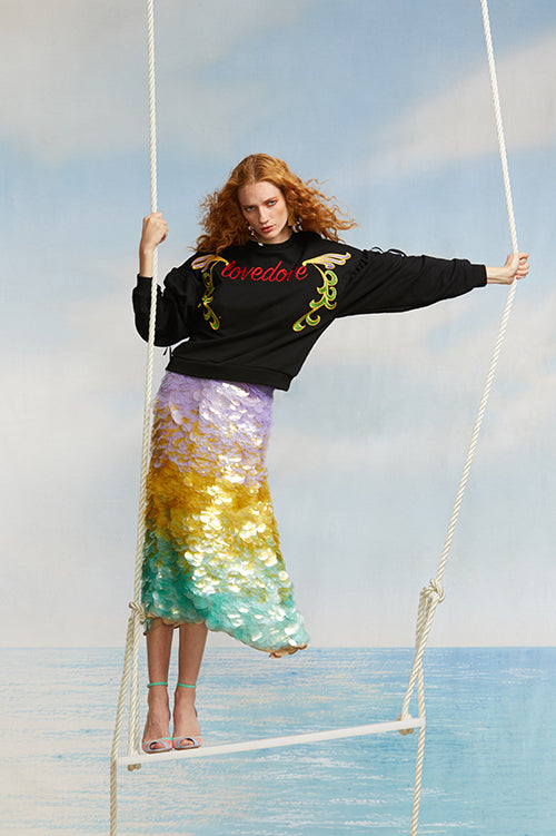 Cynthia Rowley Spring 2018 Look 33 featuring a ombre sequin skirt and black cotton sweatshirt with 'love dove' embroidered across front