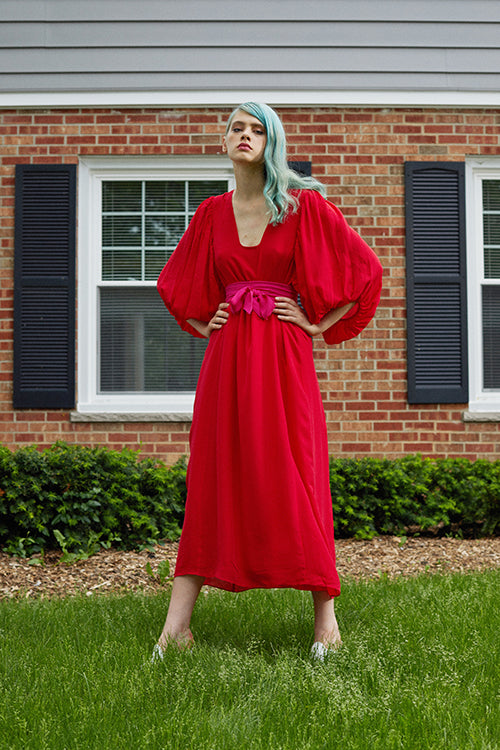Cynthia Rowley Resort 2019 Collection features a red dress belted at the high waist, flowing into a maxi length skirt.