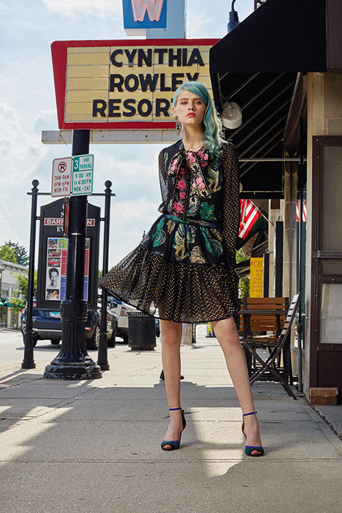 Cynthia Rowley Resort 2019 Collection features a black floral mini dress with a metallic finish paired with statement earrings, and two-toned, blue and green heels.