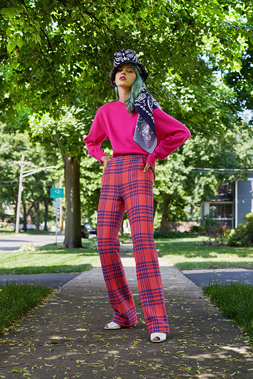 Cynthia Rowley Resort 2019 Collection features high waisted plaid pants worn with a bright pink sweater, and accessorized with a navy and white paisley hat and hair wrap.
