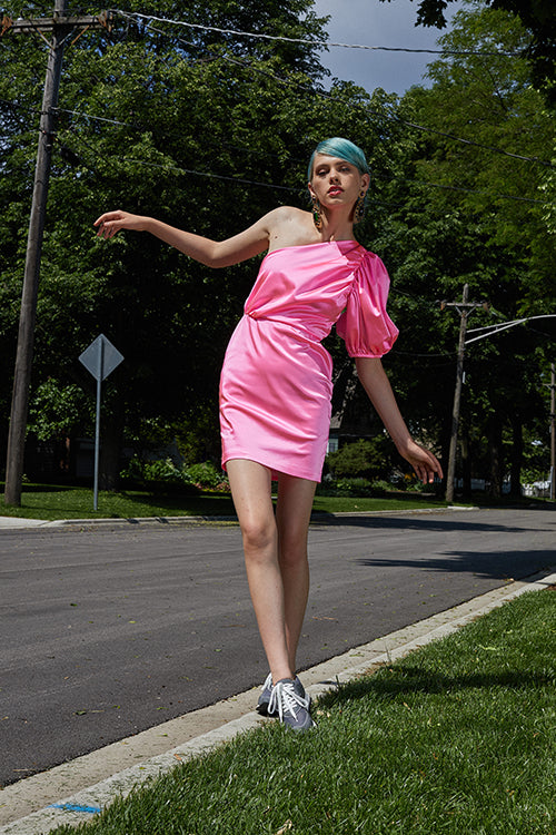 Cynthia Rowley Resort 2019 Collection features a pink silk dress with gathering along one side, paired with grey sneakers and large gold earrings.