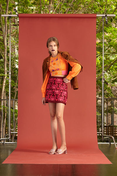 Cynthia Rowley Resort 2017 look 9 featuring a bright orange long sleeve shirt and a red printed mini skirt