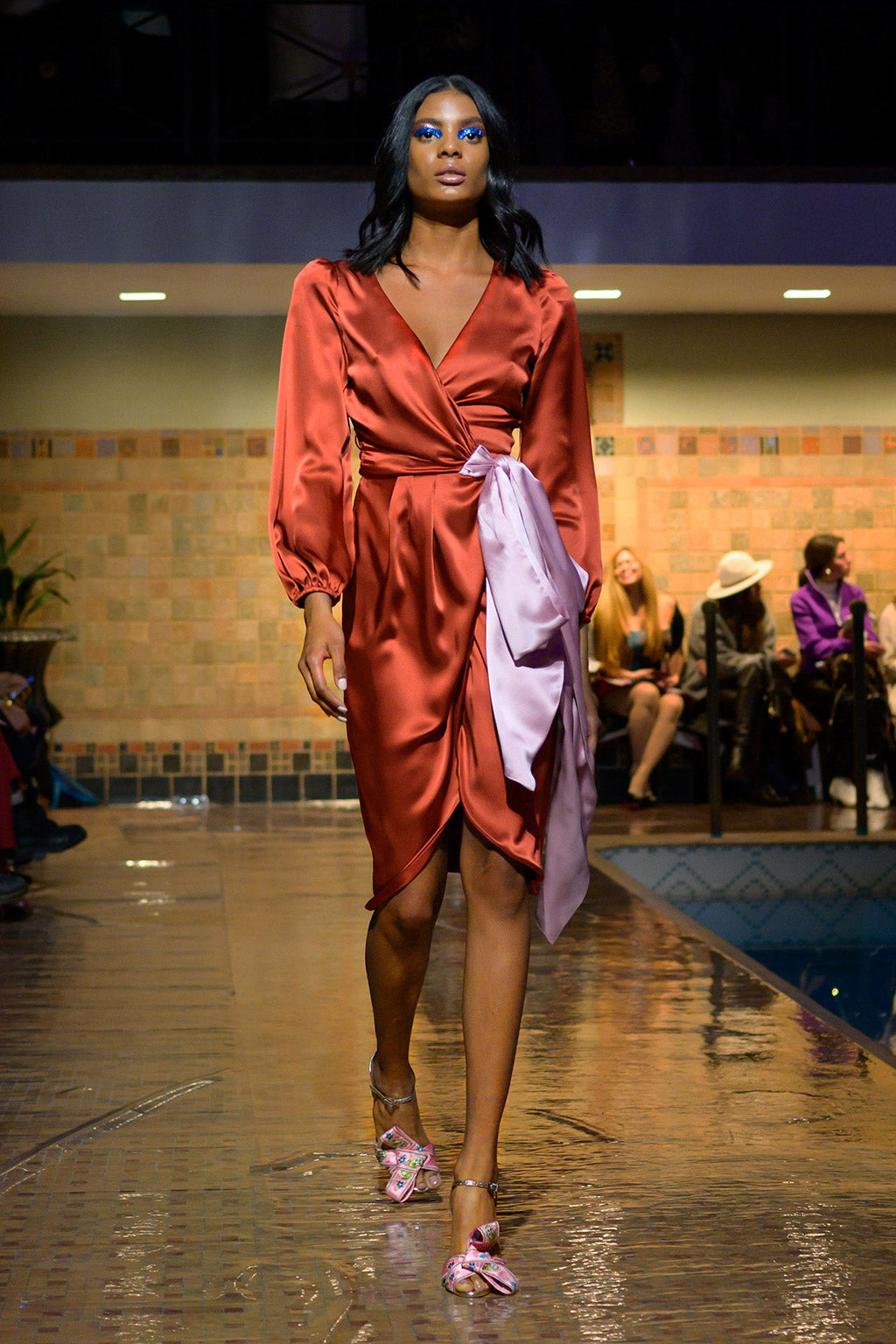 Cynthia Rowley Fall 2019 look 12 featuring an orange silk wrap dress with long sleeves and a large blush bow