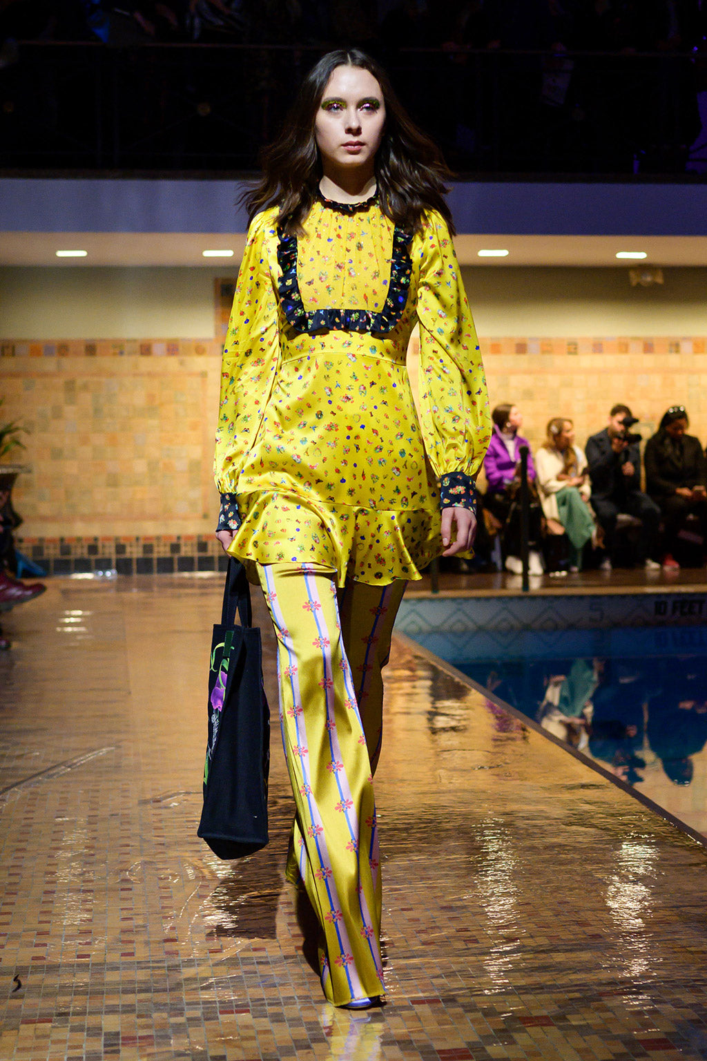 Cynthia Rowley Fall 2019 look 18 featuring a yellow printed long sleeve top with black trimming and a ruffle bottom as well as yellow printed wide leg bottoms