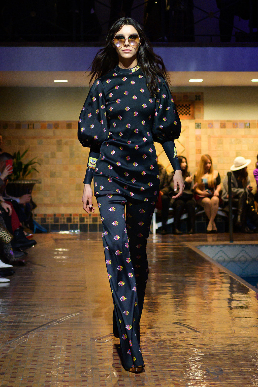 Cynthia Rowley Fall 2019 look 4 featuring a blouse in floral print with elbow length sleeves worn over a SpongeBob print Wetsuit, and pants in floral print