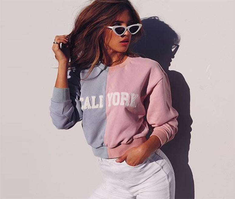 Lifestyle image featuring the CaliYork cropped sweatshirt in pink and blue.